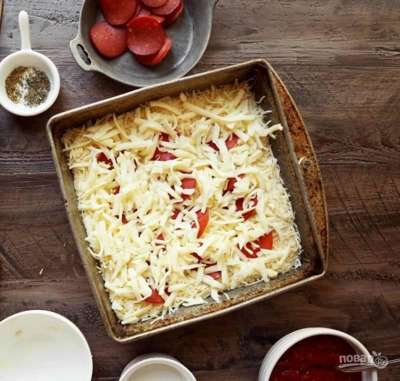 10.Натрите на крупной терке моцареллу и посыпьте пиццу по всему коржу.