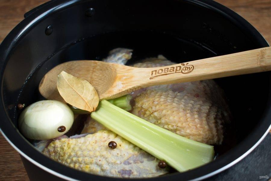 Мясо залейте водой, доведите до кипения, варите в течение 5 минут, слейте бульон. Залейте мясо свежей водой, доведите до кипения, уменьшите огонь. Добавьте очищенный лук, сельдерей, душистый перец, лавровый лист. Накройте крышкой, готовьте в течение 1-2 часов. Мясо должно легко отставать от кости. Мясо выньте, снимите с кости, бульон процедите, овощи выкиньте.