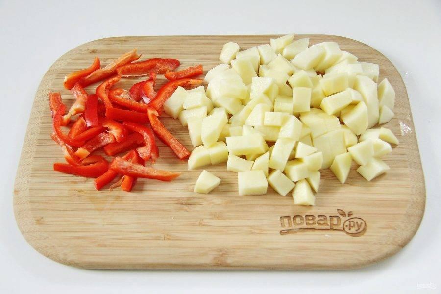 Тем временем перец нарежьте соломкой, картофель небольшими кубиками.