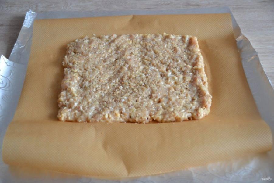 Расстелите на столе сначала фольгу, лучше 2 слоя с небольшим нахлестом. На фольгу положите бумагу для выпечки, на бумагу выложите куриный фарш в форме прямоугольника, толщиной примерно в 1,5 см.