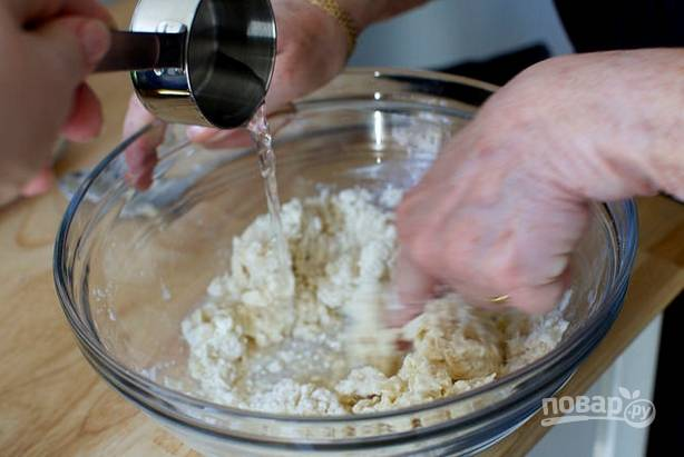 1. Для начала нужно сделать тесто. В небольшой мисочке соедините просеянную муку и щепотку соли. Добавьте масло и воду, перемешайте. Выложите в контейнер и отправьте на 10 минут в морозилку.