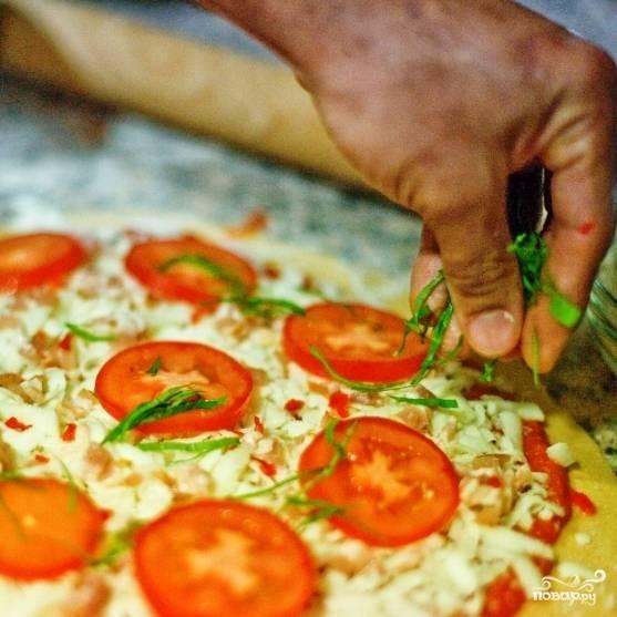 Выкладываем на пиццу тонкими ломтиками нарезанные помидоры и мелко нарубленный свежий базилик.