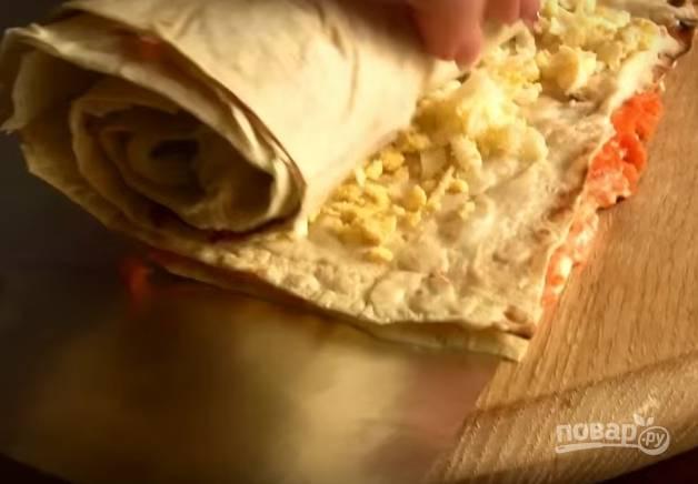6. Снова накройте всё листом лаваша, смажьте майонезом, распределите яйцо по поверхности. Затем плотно сверните рулет. Оберните его фольгой и отправьте в холодильник на 20-30 минут.