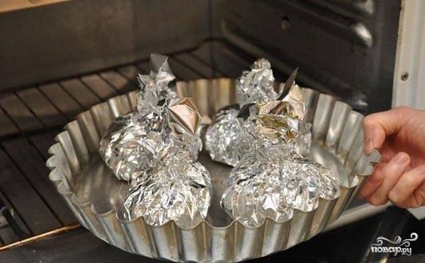 """В кусочек фольги кладите курицу. В центр филе выкладывайте грибную начинку. Скручивайте филе в форму """"бомбочки"""". Оберните курицу фольгой. Отправляйте в духовку, разогретую до 200 градусов на 30-35 минут. После чего разверните фольгу и готовьте еще 10 минут."""