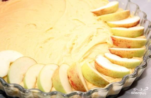 4. Получившуюся густую массу выложите в промасленную форму. Лопаткой разровняйте тесто. Сверху выкладывайте порезанные дольками яблоки. Старайтесь уложить их плотно – лучше внахлест.