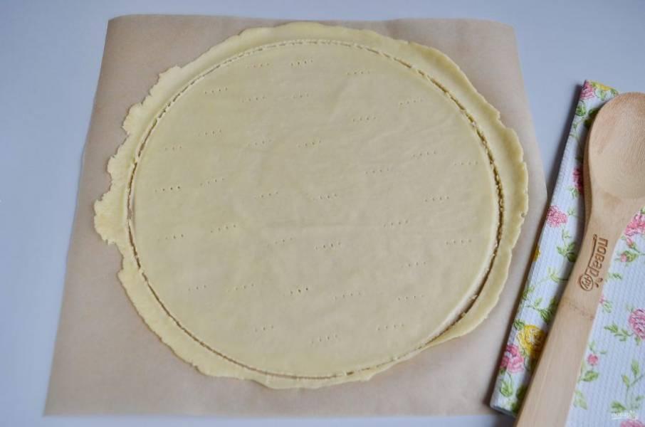 Отрежьте два квадрата пергамента. Коржи пекутся очень быстро. Разогрейте духовку до максимума. Каждый комочек теста раскатывайте максимально тонко, толщина не  более 1 мм. С помощью тарелки или крышки с ручкой ножом отрежьте круг теста. Поставьте в таком виде в духовку и выпекайте каждый корж по 3-5 минут.