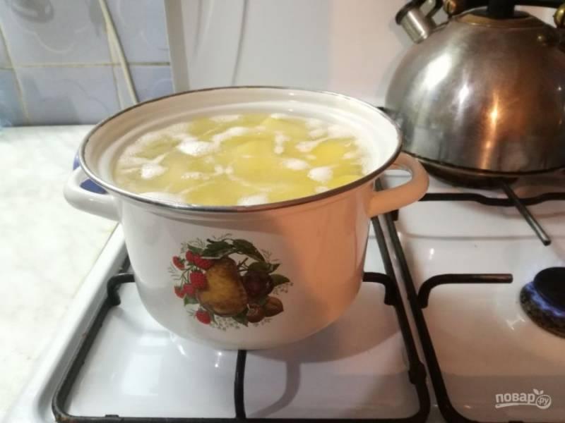 Очищенный картофель поре;mnt на 3-4 части и положите в кастрюлю с водой. Доведите до кипения и варите 5 минут.
