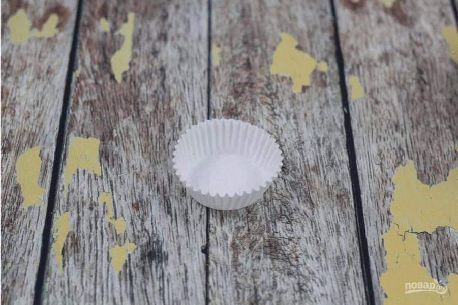 4. Теперь соберите конфету. В бумажную формочку влейте немного глазури. Выложите половинку печенья. Затем снова глазурь, и опять печенье. А сверху вновь глазурь.