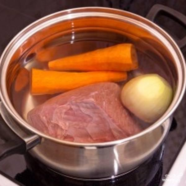 В кастрюлю сложите промытую говядину, 1 очищенную морковку и 1 очищенную луковицу. Залейте холодной водой и варите под крышкой 2 часа (время от времени снимайте пенки). В конце варки добавьте соль и лавровый лист.