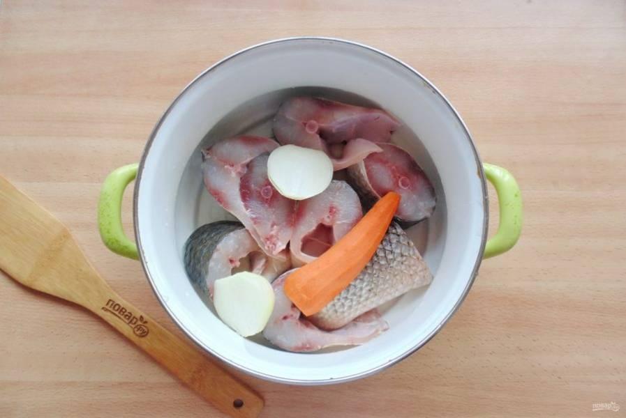Добавьте очищенный репчатый лук и морковь.