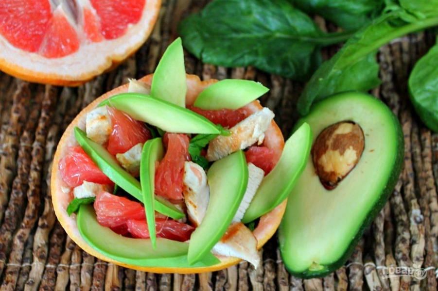 Далее, кладем кусочки грейпфрута. Авокадо чистим, режем тонкими дольками и добавляем в салат.