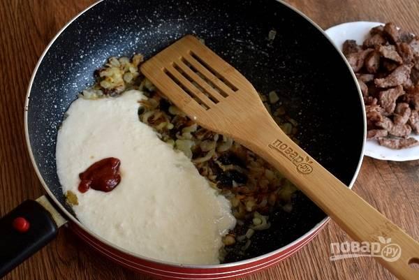 Добавьте сметану, томатную пасту, перемешайте. Влейте горячую воду, прогрейте полминуты.