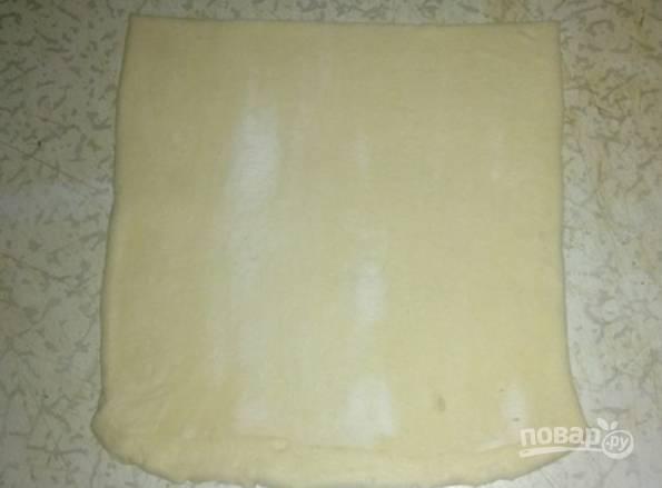 Разморозьте слоеное тесто. Затем разрежьте на полосочки по 10-12 см шириной. Каждую полоску раскатываем в квадратик.