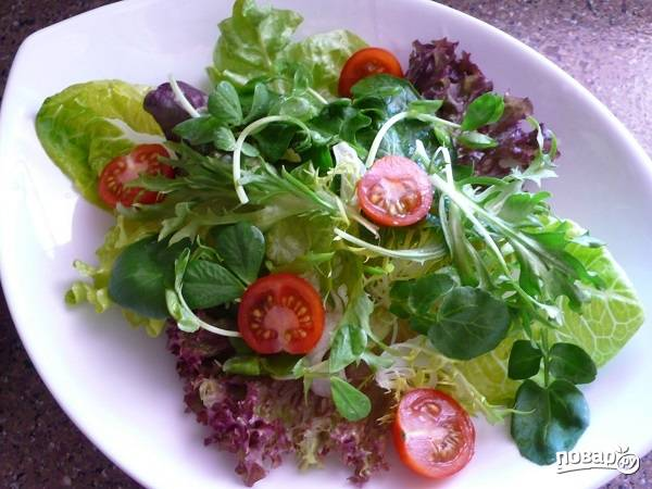 1. Сам процесс приготовления невероятно прост и не займет у вас больше 10 минут. Листья салатов вымойте, обсушите и выложите на тарелку для подачи. Помидорки нарежьте пополам.
