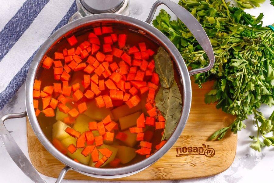 Очистите морковь от кожуры, промойте и нарежьте мелкими кубиками. Добавьте в кастрюлю и отварите еще 2-3 минуты.