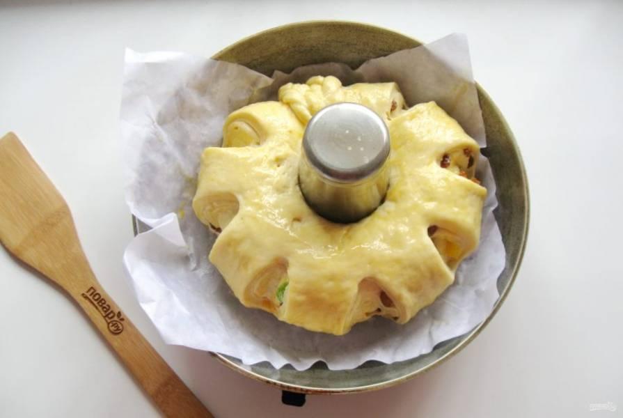 Поставьте пирог в теплое место на 30-35 минут для расстойки. Через это время он немного подойдет. Смажьте пирог яйцом.