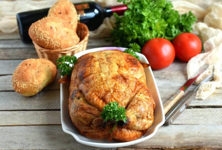 Уложите курицу в форму, смажьте топленым маслом и запекайте при температуре 180 градусов минут 45, периодически поливая курицу образовавшимся соком.  Минут через 20 можно накрыть курицу фольгой. По истечению времени аккуратно проколите курицу тонкой шпажкой в середине. Сок из прокола должен быть абсолютно прозрачным. В противном случае пеките курицу еще немного. Снимите фольгу и увеличьте температуру. Подрумяньте корочку. Готовую курицу выложите на блюдо и накройте фольгой минут на 20, чтобы соки равномерно распределились по курице и блюдо вышло не сухим. Украсьте курицу зеленью и подавайте.