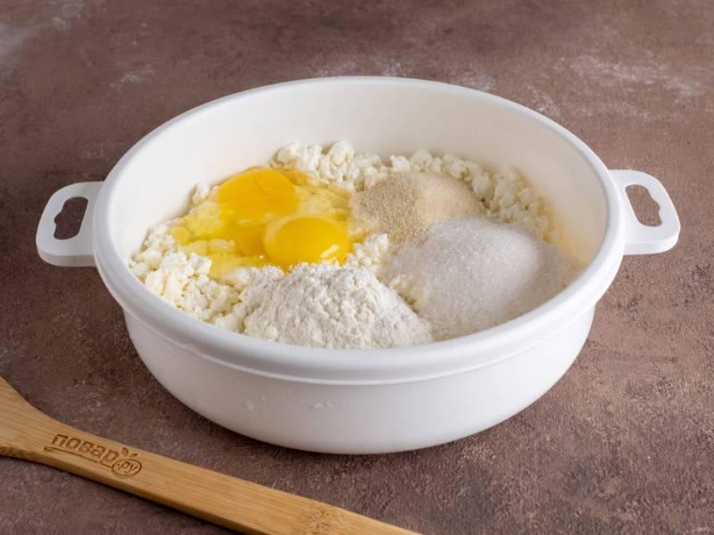 """В творог добавьте манку, яйцо, сахар и муку. Тщательно перемешайте, помните. С добавлением муки ориентируйтесь по влажности теста. Дайте тесту постоять 7-10 минут, чтобы """"заработала"""" манка."""