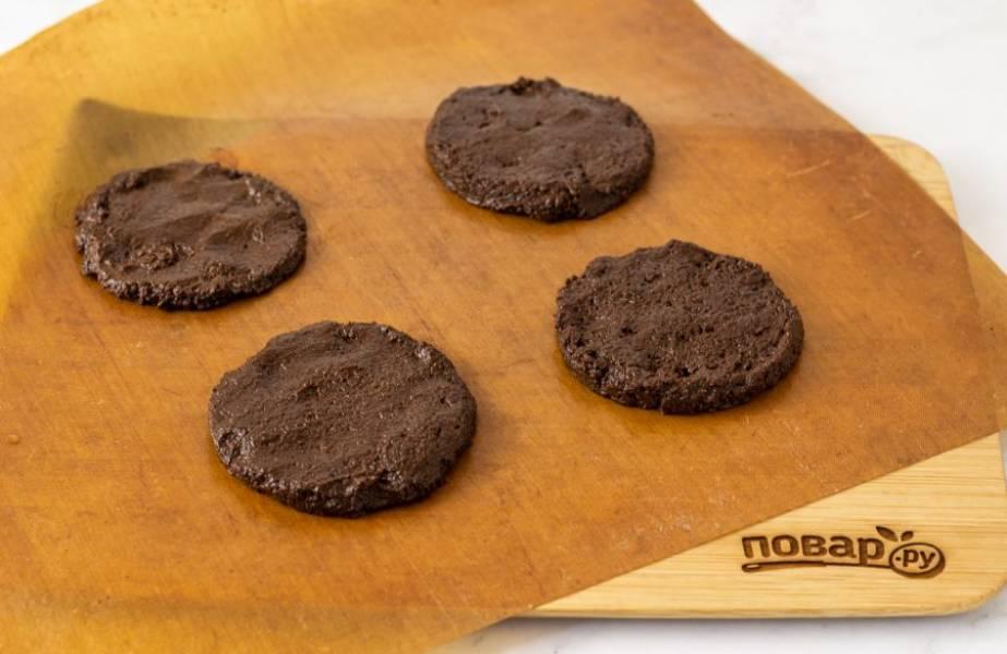Выложите с помощью кулинарного кольца круглые печенья на пергамент для выпечки. Влажными руками немного сгладьте форму.