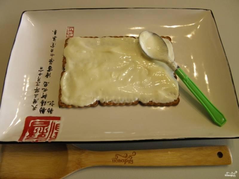 Возьмите теперь плоскую тарелочку (квадратную или прямоугольную). Выложите на неё первый слой печенья. Смажьте его очень щедро кремом.