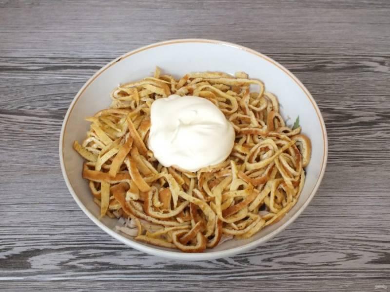 В салатник переложите обжаренные овощи, кальмары, яичные блинчики и заправьте майонезом. Добавьте по вкусу соль.