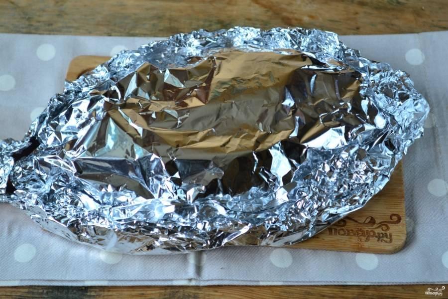 Сверху накройте фольгой и скрепите ее края, чтобы внутрь не попадал воздух. Отправьте рыбу в духовку на 45-50 минут. За 10 минут до конца фольгу раскройте.