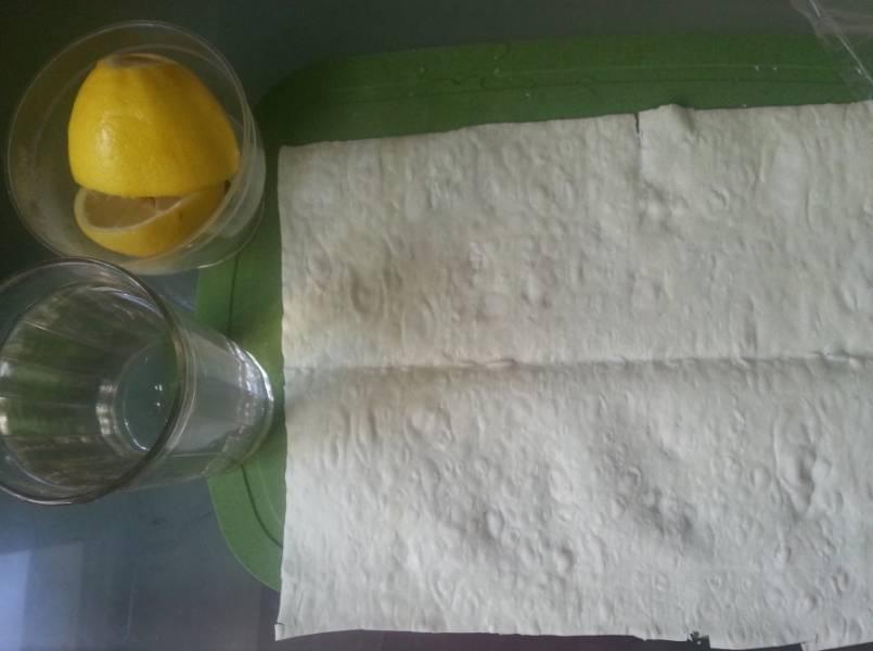 Из лимона выдавить сок и добавить в воду. Лаваш слегка сбрызнуть водой с лимонным соком.