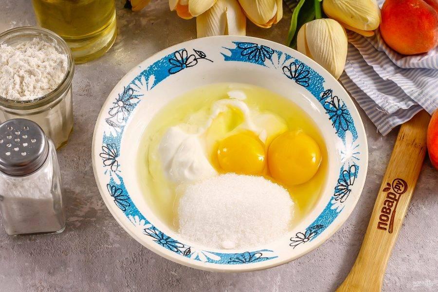 Соедините в другой емкости сахар, сметану любой жирности и два куриных яйца. Тщательно взбейте.