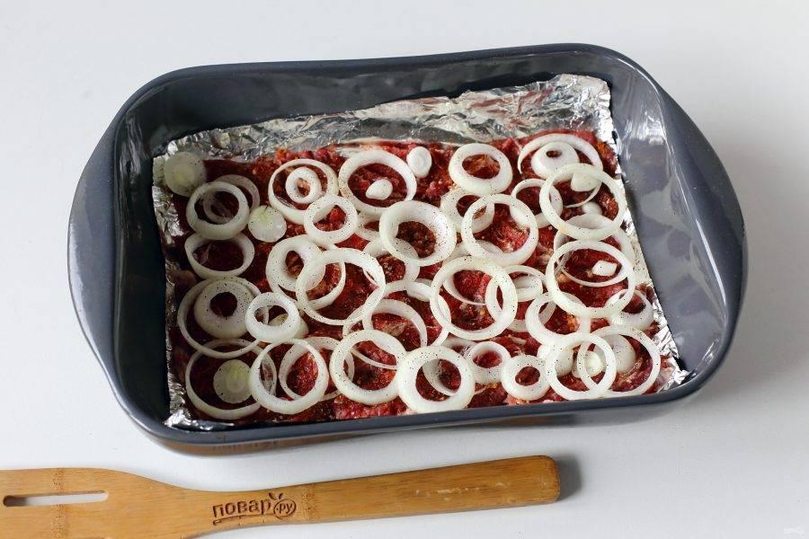 Сверху выложите нарезанный кольцами лук. Посыпьте лук солью и молотым перцем.