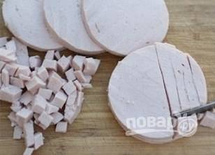 Колбасу очистите от пленки и нарежьте кубиком.