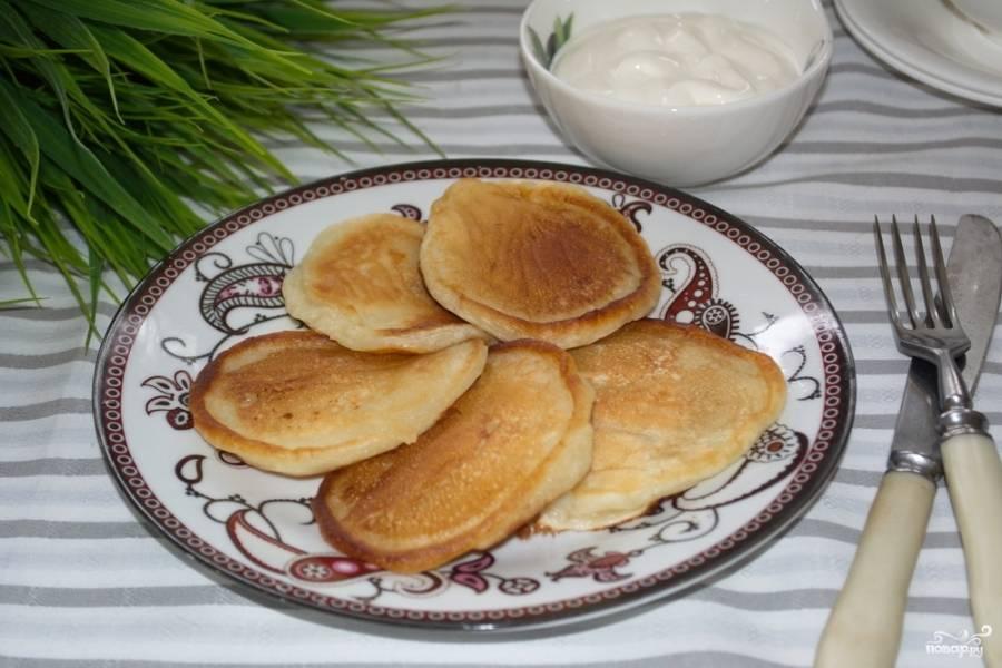 Подавайте вкусные оладьи на кефире  со сметаной. Вместо сметаны можно использовать джем или варенье. Тут уж ориентируйтесь на собственные предпочтения.