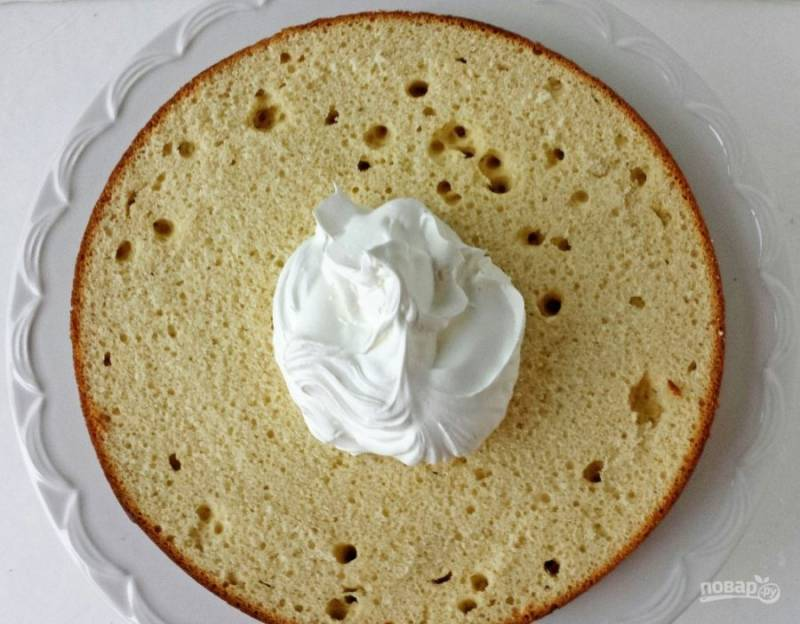 14.На блюдо выкладываю одну половинку, на нее кладу немного крема и размазываю его по всей поверхности.