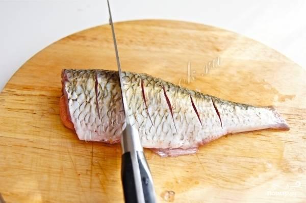 Поперёк рыбы сделайте несколько надрезов.