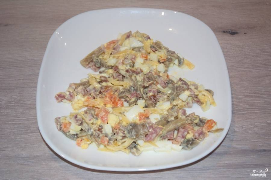 Заправьте салат сметаной или майонезом. На плоское блюдо выложите салат в форме елки.