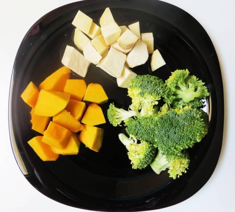 Первым делом как следует промойте все необходимые овощи. Затем обсушите тыкву и картофель очистите от кожуры и нарежьте кубиками, а брокколи разберите на соцветия.