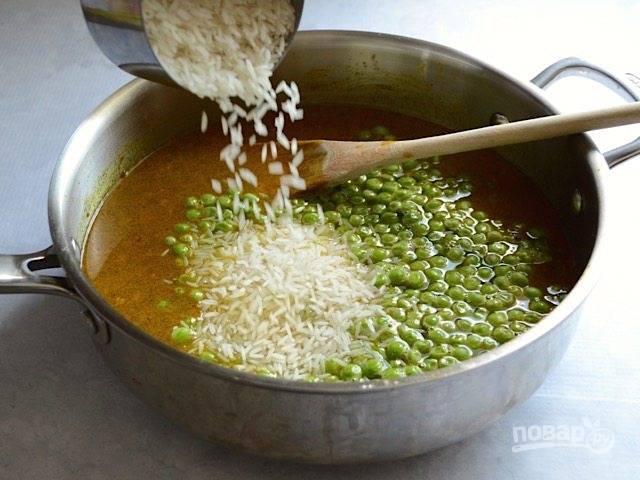5.Всыпьте рис и зеленый горошек, перемешайте.