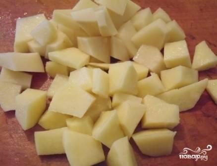 Очистим картофель, нарежем его небольшими кубиками и отправим в готовый бульон. Куриную ножку достанем, и, когда слегка остынет, отделим мясо от костей.