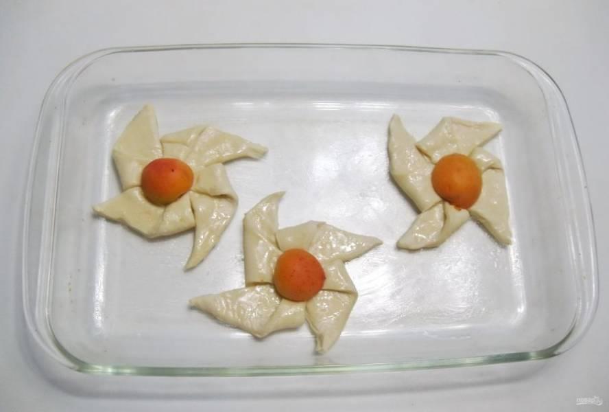 Приготовленные слойки переложите в форму для выпекания. Смажьте их абрикосовым вареньем или джемом.