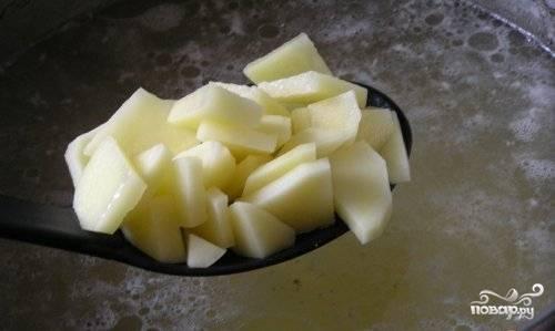 Поставьте бульон на огонь до закипания. Картофель помойте, почистите, нарежьте. Добавьте в кипящий бульон.
