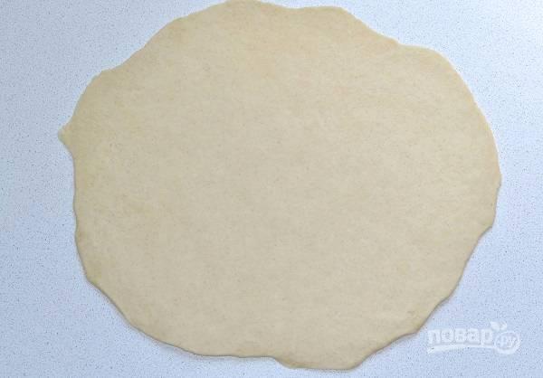 Отщипните кусочек теста и раскатайте его тонким пластом. Я сразу вырезаю ровный круг, но можно выпекать и так.