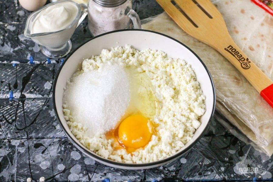 Выложите в глубокую миску творог любой жирности, разомните его, чтобы не остались крупные кусочки. Выложите сметану любой жирности, оставляя около 3-4 ст.л. для заливки. Добавьте сахар, оставляя 1 ст.л. для заливки. Всыпьте соль, вбейте куриные яйца. Тщательно перемешайте всю начинку, чтобы она стала практически однородной.