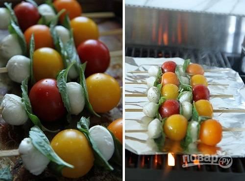 2. На шпажку нанизайте по 2 помидора, 2 шарика сыра и 2-3 листочка базилика. На разогретый гриль выложите лист фольги и на него отправьте шпажки. Полейте немного оливковым маслом, посолите и поперчите немного.