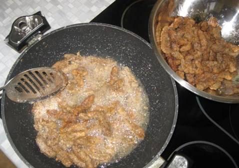 При помощи шумовки обжаренные кусочки (обжариваем по 7-10 минут) достаем и кладем в термостойкую посуду.