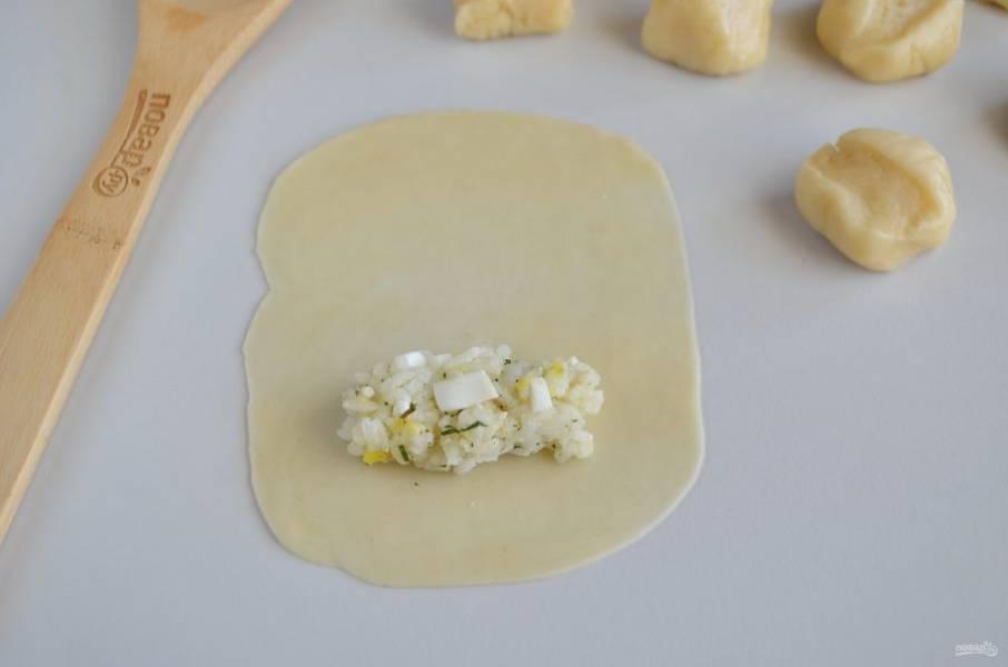 Разделите тесто на 15 частей, каждую очень тонко раскатайте в прямоугольник. Положите часть начинки.