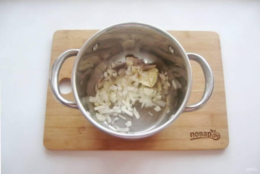 Репчатый лук очистите, помойте и нарежьте. Выложите в кастрюлю. Добавьте сливочное масло.