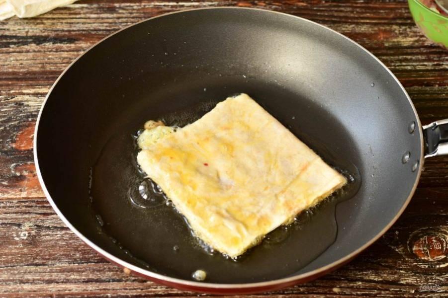 В сковороде разогрейте растительное масло. Выложите лаваш с фаршем.