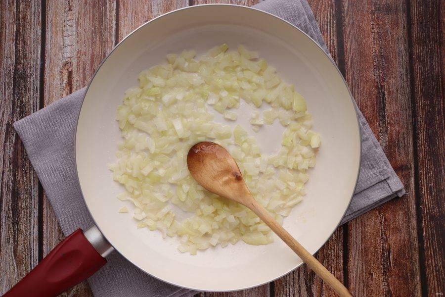 В сковороде разогрейте 3 столовые ложки подсолнечного масла и обжарьте мелко нарезанный лук до прозрачности.