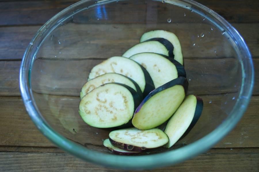 Баклажаны нарезаем колечками. Кладем в миску. Солим (1 ч. ложка соли) и вливаем 1 стакан воды. Оставляем на 30 минут. Этот шаг можно и пропустить, если используете свежие молодые овощи.