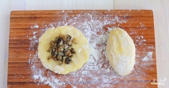 3.  Когда картофель остынет, разминаем его, добавляем немного  муки, соль, специи по вкусу и муку. Перемешиваем массу до однородной консистенции. Присыпаем плоскую поверхность мукой (в моем случае - это разделочная доска), выкладываем часть картофеля - это будет основа, а в середину добавляем начинку из лука и грибов. Теперь края нужно слепить удобным для вас способом (по типу пирожков).