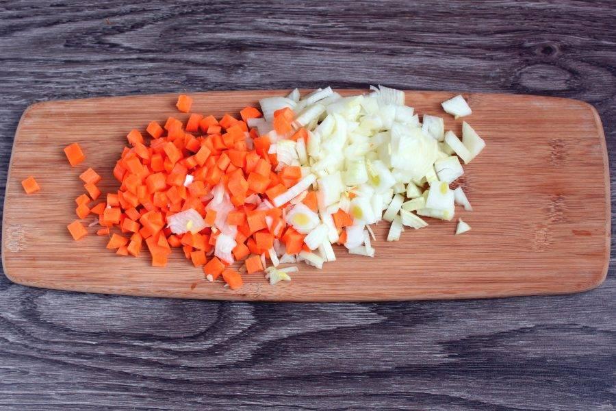 Добавьте лук и морковь, нарезанные кубиком и продолжайте жарку до смягчения овощей.